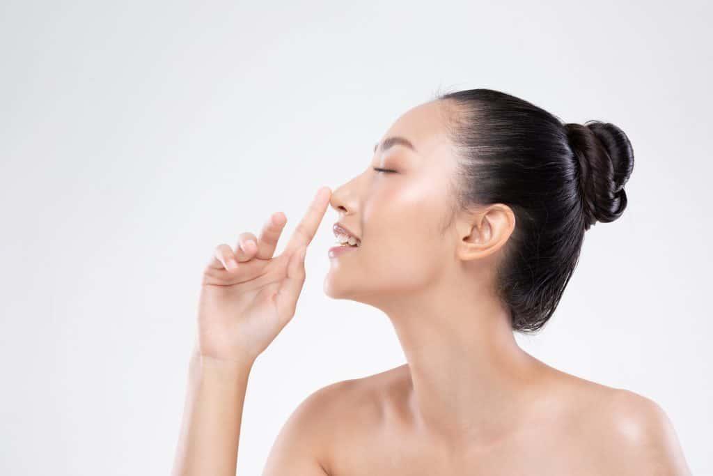 אישה נוגעת באף שלה לאחר ניתוח